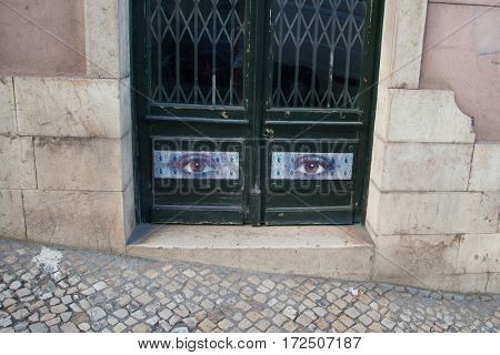 Street in Portugal. Old building with a door decorated by picture with woman's eyes, Lisbon, close-up view
