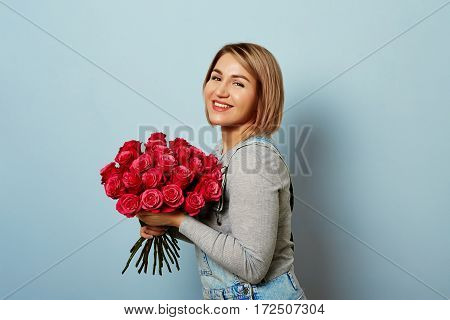 Beautiful girl in the overalls with red roses in hands on a blue background. Bouquet of roses