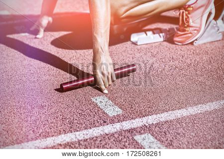 Female athlete ready to start relay race on running track