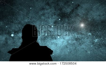 Lonesome girl looking at the night sky.