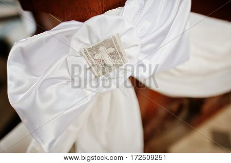 White Ribbon Decoration With Cross At Church Ceremony Of Wedding.