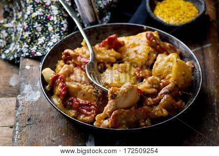 Braised chicken with dried tomatoes in frying pan.selective focus