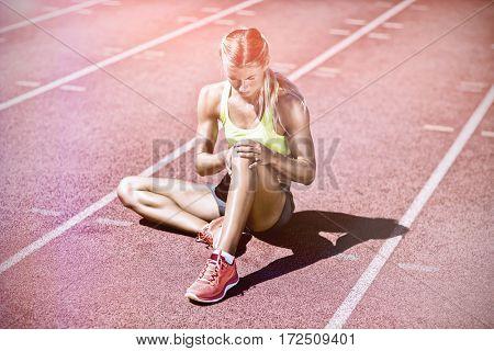 Female athlete warming up onrunning track on sunny day