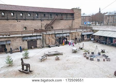NARVA, ESTONIA - JANUARY 2, 2017: People in Northern Yard of Hermann Castle Museum. This place looks like in the 17th century. There are four workshops and apothecary in the yard.