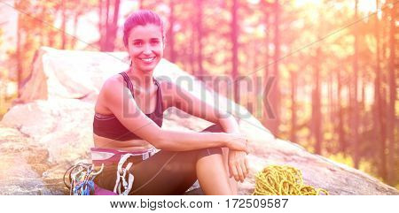 Woman smiling and sitting on a rock with climbing equipment