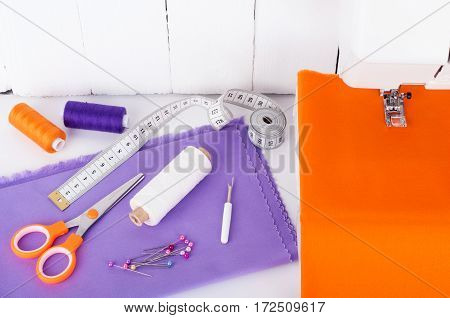 Sewing background concept. Sewing machine with sewing utensils for needlework - cotton fabric spools of thread scissors measuring tape on white wooden background