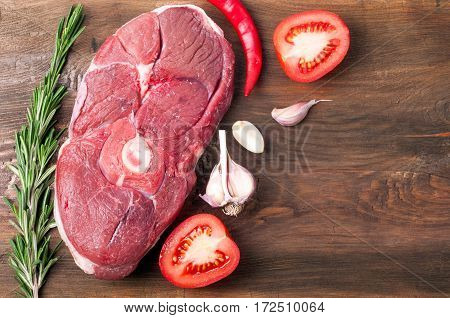 Raw meat mutton steak with rosemary, chili pepper, garlic and tomatoes on rustic wooden background. Ingredients for cooking. Top view