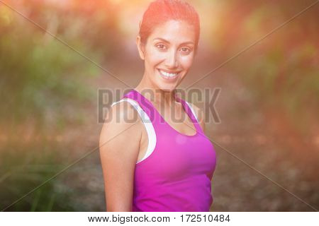 Portrait of smiling fit woman standing in park