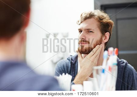 Bearded young man looking in mirror in the morning