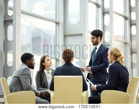 Confident employee sharing his working plan or financial analysis with co-workers