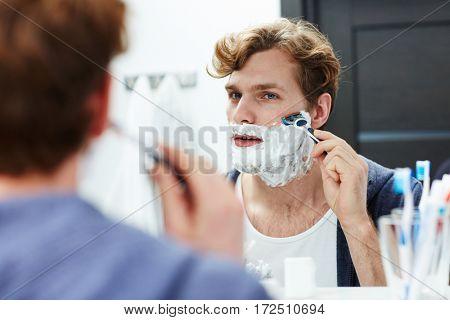 Attractive man shaving his beard in bathroom