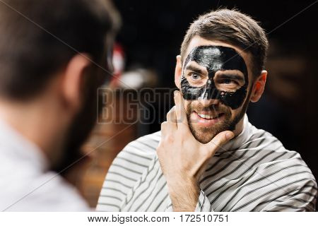 Mirror reflection of handsome man with peel-off mask on face