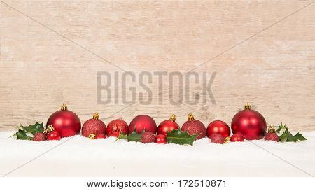 Row of red christmas balls decoration in the snow on a wooden background