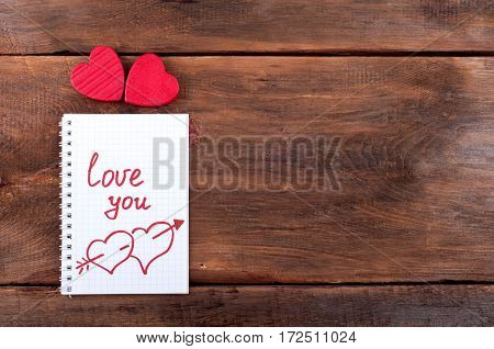 Valentines day background. Valentine heart and open page notebook with the written word Love you on old wooden background. Top view