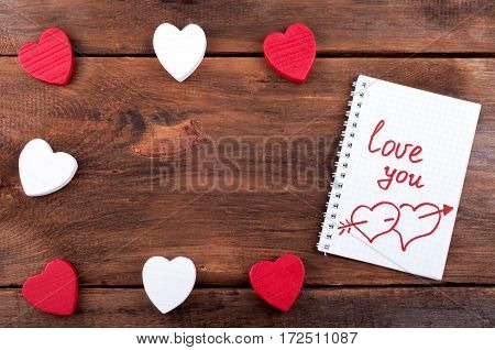 Valentines day background. Valentine heart and open page notebook with the written word Love you on old wooden background. Valentine card. Top view