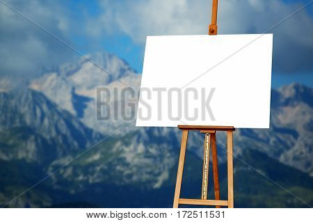 Blank painter artist canvas on easel with mountain in background copy space for artistic picture or painting
