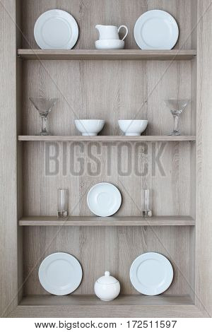 regiment of gray chipboard decorated with kitchen utensils, glasses and wine glasses in the dining area