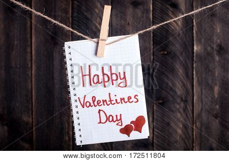 Note with written words Happy Valentine's Day hanging on the clothesline. Valentine background on old wooden boards