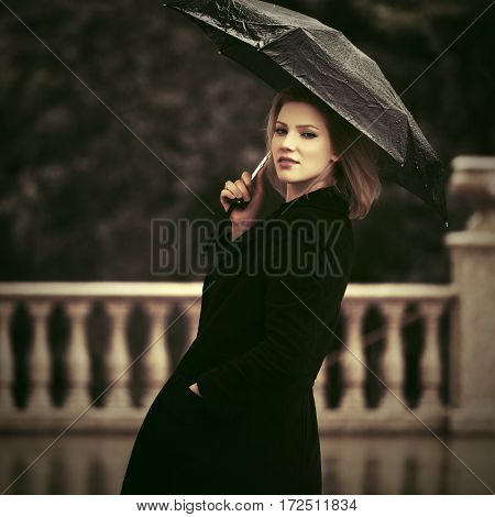 Happy woman with umbrella walking in the rain. Stylish fashion model outdoor