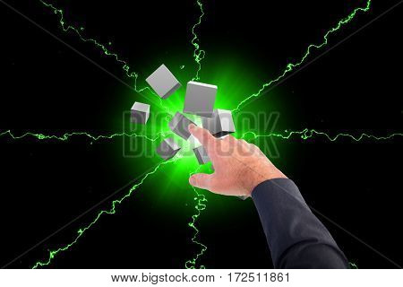 Businessman pointing with his finger against digitally generated grey cubes floating