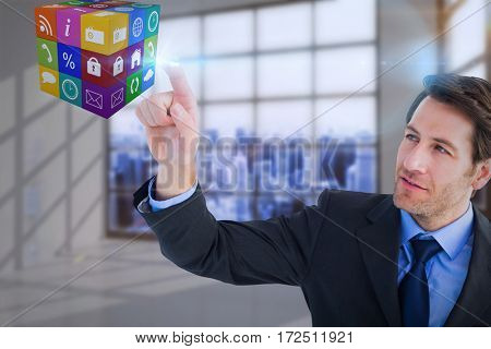 Serious businessman pointing at cube against room with a lot of windows