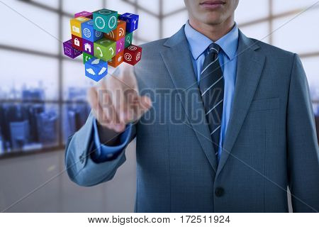 Midsection of well dressed businessman pointing cube against room covered with windows