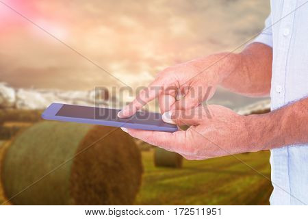 A man using tablet computer against scenic backdrop