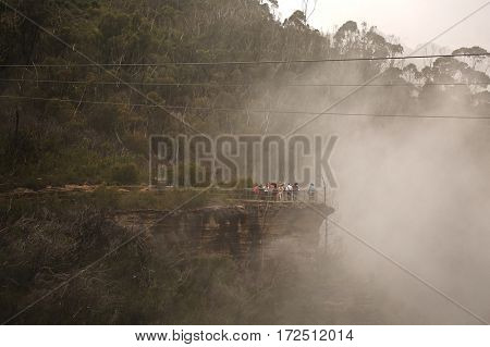 KATOOMBA, AUSTRALIA - APRIL 3, 2014: People on the scenic path in misty weather.