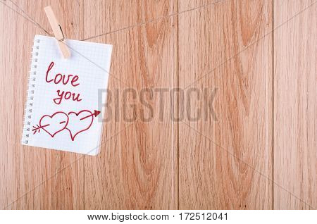 Note with inscription Love you hanging on the clothesline. Valentine background concept with copy space on wooden boards