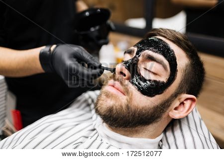 Relaxed man having purifying mask on face