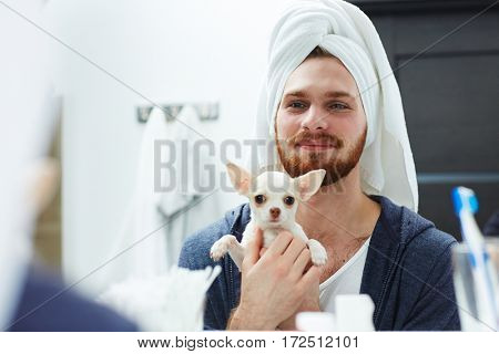 Man with towel on his head holding chiwawa puppy in front of mirror