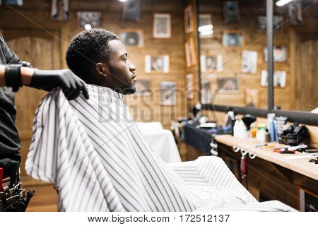 African guy sitting in barbershop covered by napkin
