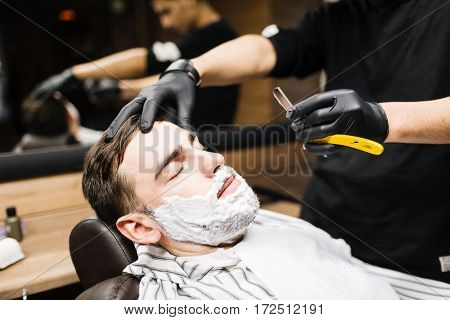 Man with foam on face having his beard shaven
