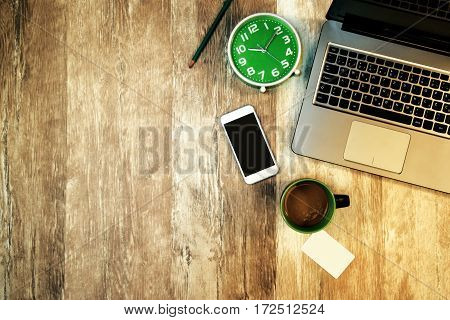Top view of office desk and workspace as copy space with laptop computer clock cup of coffee business card and smartphone