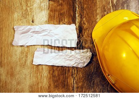 Top view of yellow hard hat and crumpled paper as copy space on wooden desk