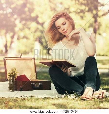 Young blond woman reading a book in city park. Stylish fashion model outdoor