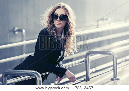 Young business woman on city street. Stylish fashion model in sunglasses outdoor