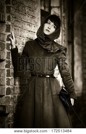 Sad young woman in headscarf next to brick wall. Stylish fashion model outdoor