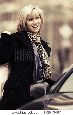 Happy young woman with shopping bags next to car. Stylish fashion model outdoor