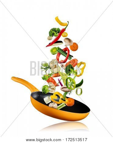 Fresh vegetables flying into a pan, isolated on white background