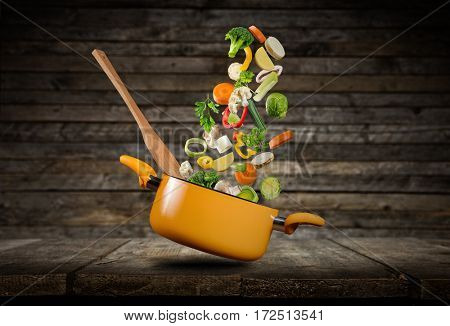 Fresh vegetables flying into a pot, placed on wooden planks