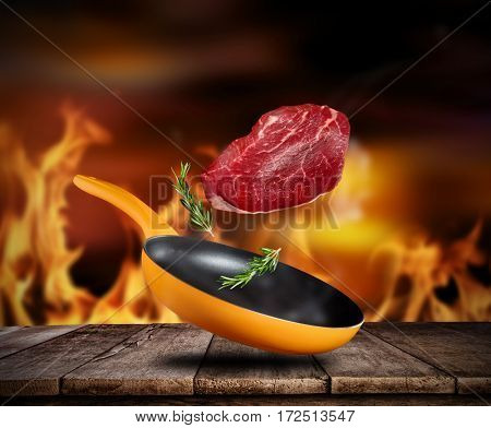 Fresh beef steak flying into a pan, placed on wooden planks, fire on background