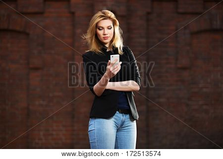 Young blond business woman using smart phone on city street. Stylish fashion model outdoor