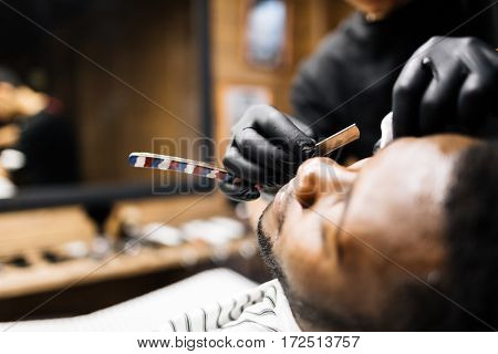 Barber shaving face of his client