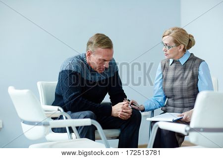Anxious man consulting with psychologist about his problem