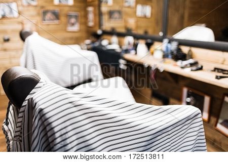 Empty armchairs with striped napkins in barbershop