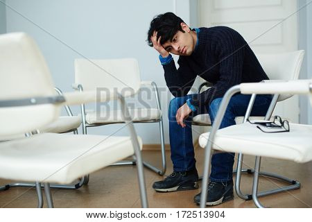 Adolescent man sitting on chair and touching his head