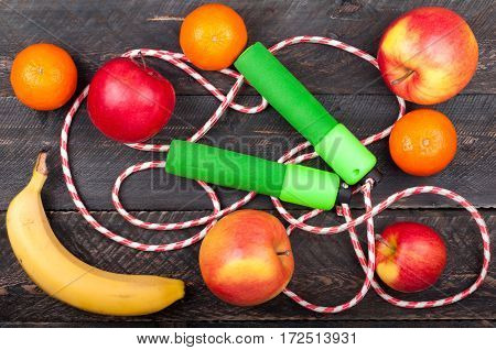 Jumping rope and fruits on old wooden floor. Sport and healthy life concept background. Skipping rope babana apples and citrus on dark wooden background. Top view