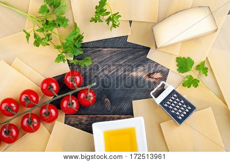 Ingredients for cooking lasagna. Lasagna parmesan cheese cherry tomatoes olive oil and herbs on a wooden rustic background. Italian food. Top view