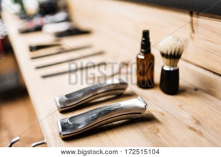 Electric razors, shaving brush and spray bottle on wooden table